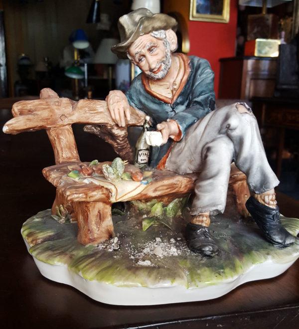 Statua originale di Capodimonte raffigurante vecchio su panchina con vino